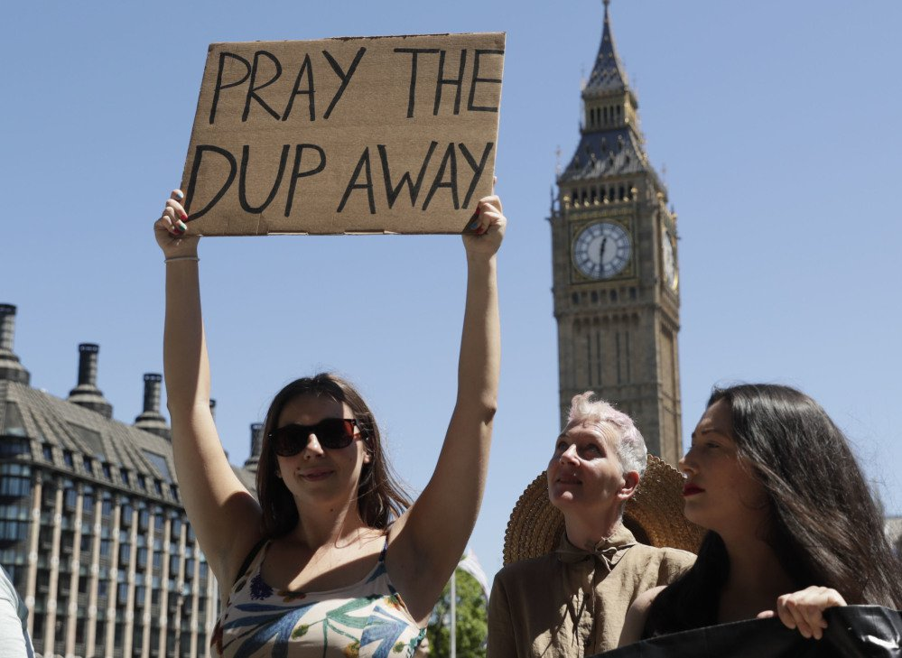 People demonstrate in Parliament Square in London against the Conservative and Northern Irish party agreement that was reached after Britain's general election Saturday.