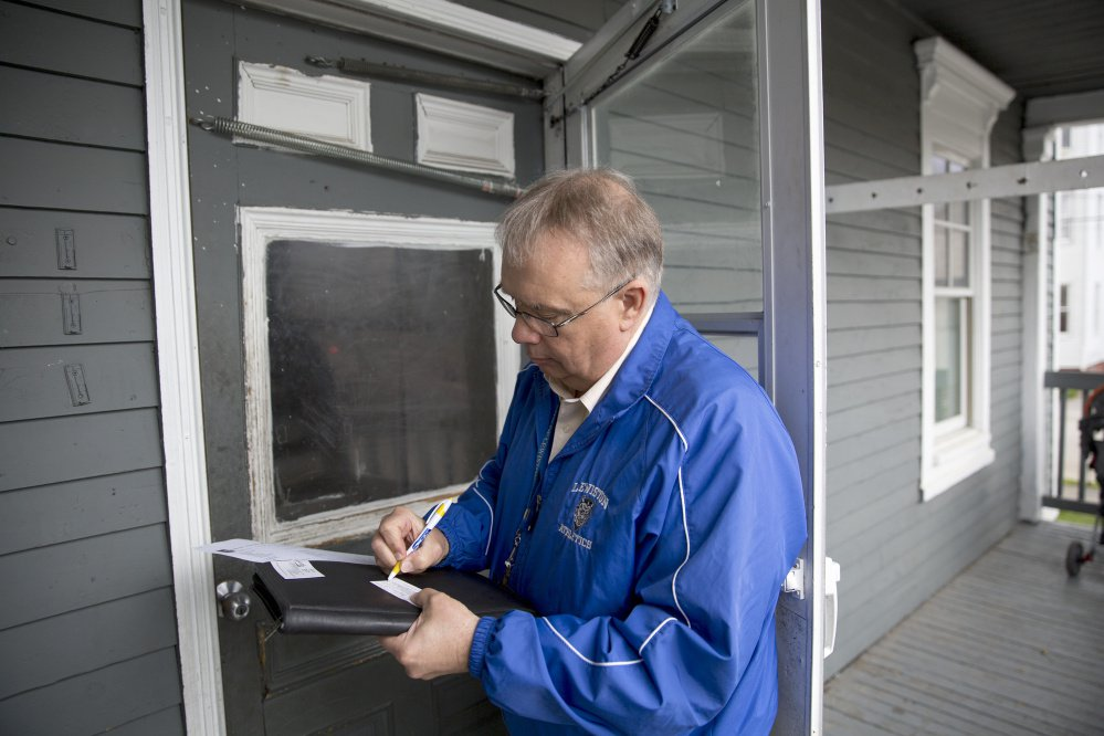 Truancy officer Butch Pratt writes down his number and a note to leave on the door of an apartment where he hoped to discuss a student's absenteeism. Pratt said most parents do call him back if they aren't home.