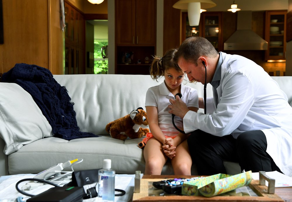 Claire Bennett, 8, watches as Dr. Adam Lowry examines her at her family's home in Great Falls, Va. The girl needed a last-minute physical for summer camp.