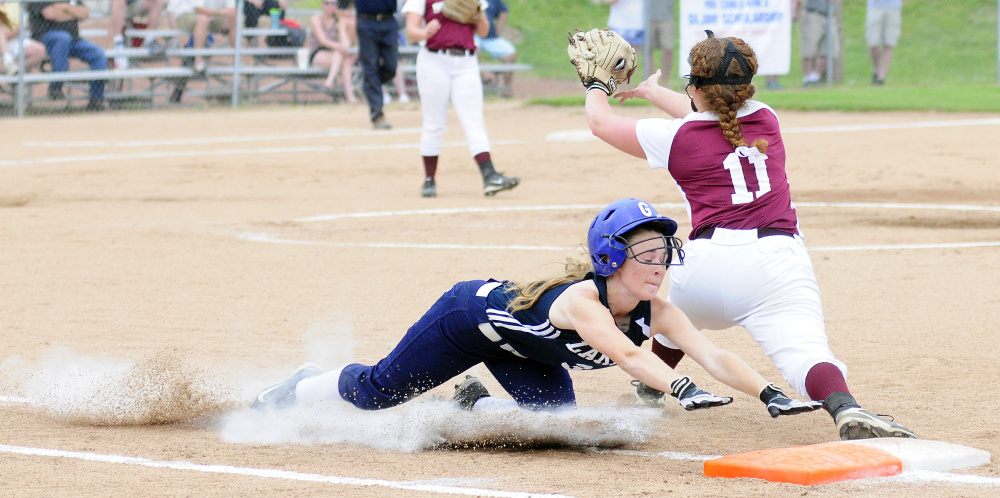 Greenville's Jessica Pomerleau slides safely into first base as Richmond's Cassidy Harriman waits for the throw during the Class D South regional final Tuesday at St. Joseph's College in Standish.