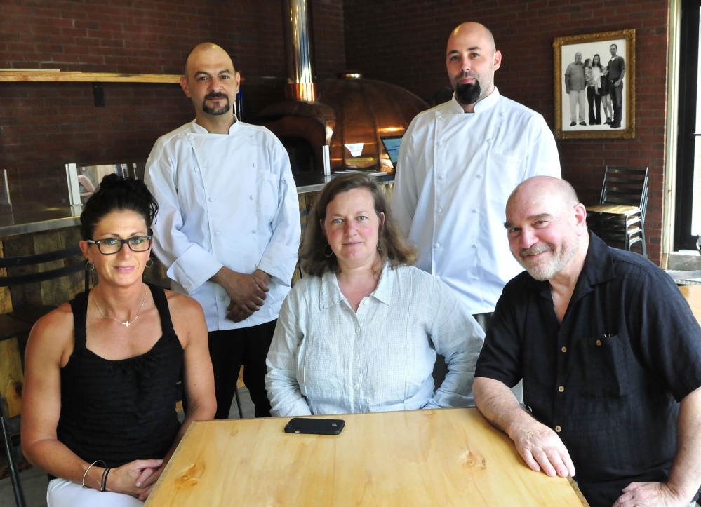 Ready to work at The Miller's Table at Maine Grains in Skowhegan on Tuesday are co-founders Amber Lambke, center, and Jon Kimbell, right, with General Manager Erin Savage, left. Standing are chefs Matthew Crate, left, and Lucas Cates.
