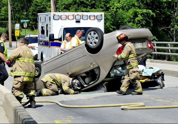 Waterville firefighters, including Chief Dave Lafountain lying on pavement at right, remove the driver of this vehicle that overturned in the middle of Thayer Memorial Bridge on Gilman Street in Waterville on Monday.