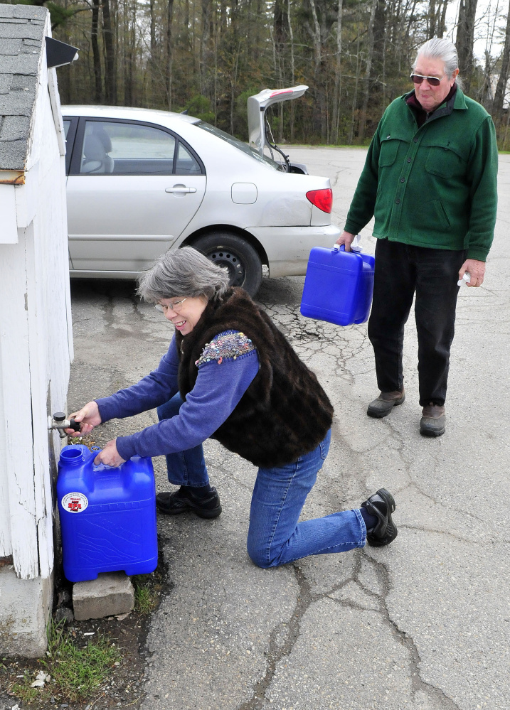 Connie Bellett and her husband, Phil Frizzell, fill water containers May 10 at the Windsor Town Office. The couple transported the water 8 miles to the Community Garden in Palermo to water growing vegetables. The Malcolm Glidden American Legion Post 163 has refused to connect a water supply to the rental space.