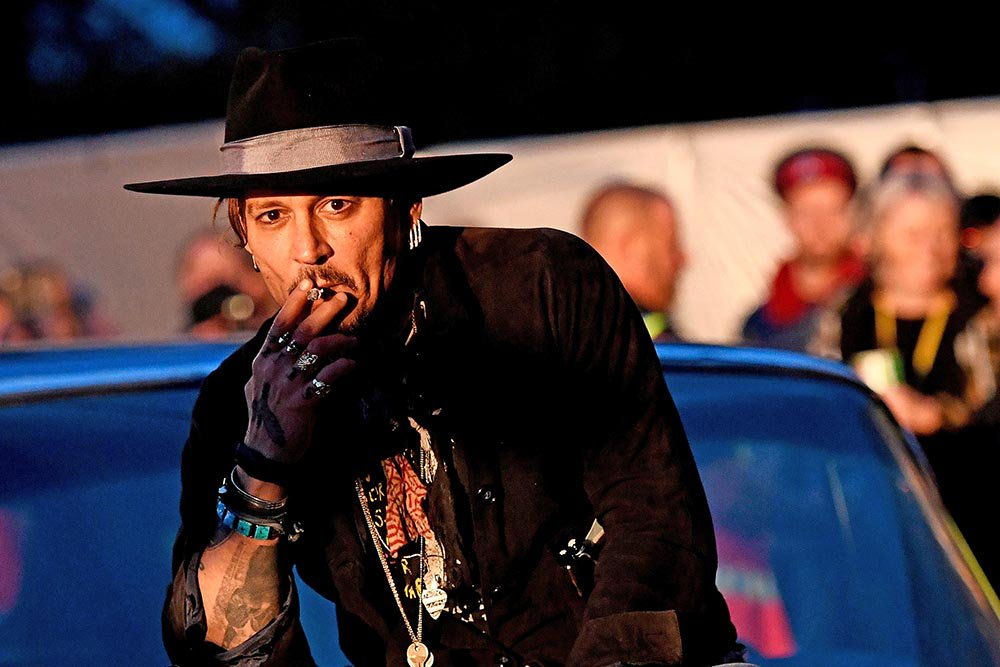 """Johnny Depp poses on a Cadillac before presenting his film """"The Libertine,"""" at Cinemageddon during the Glastonbury Festival in Britain, on Thursday."""