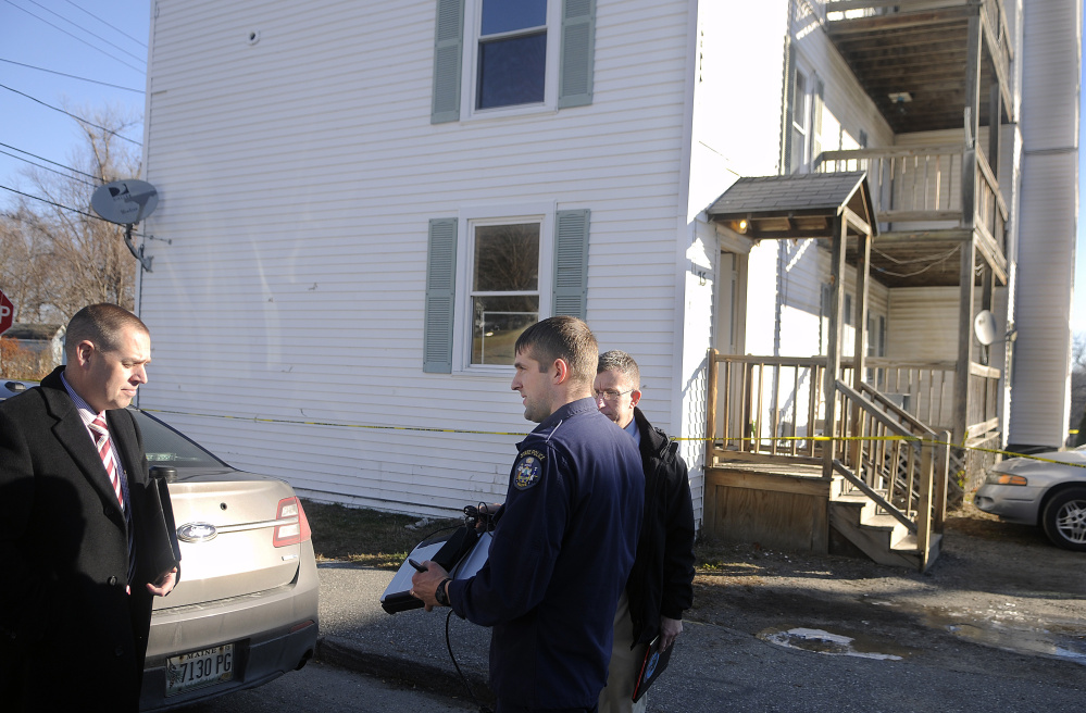 State police detectives confer Nov. 24, 2015, outside an apartment building on Washington Street in Augusta, where a homicide occurred.