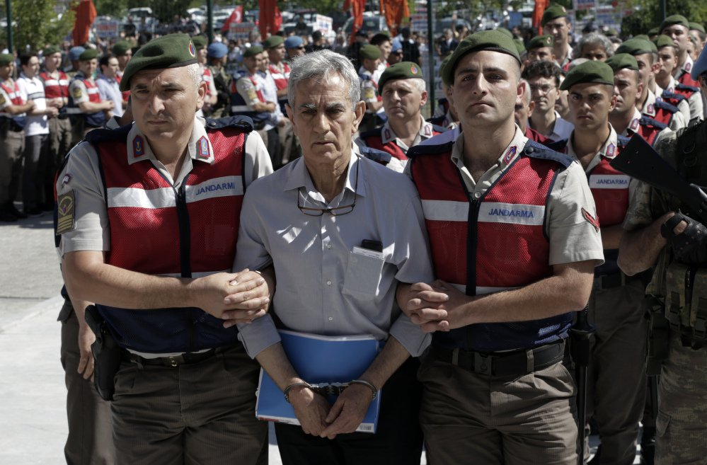 Akin Ozturk, Turkey's former Air Force commander, and dozens of the other 500 coup suspects are escorted by paramilitary police to a courthouse in Ankara on Monday. ed Press/Burhan Ozbilici