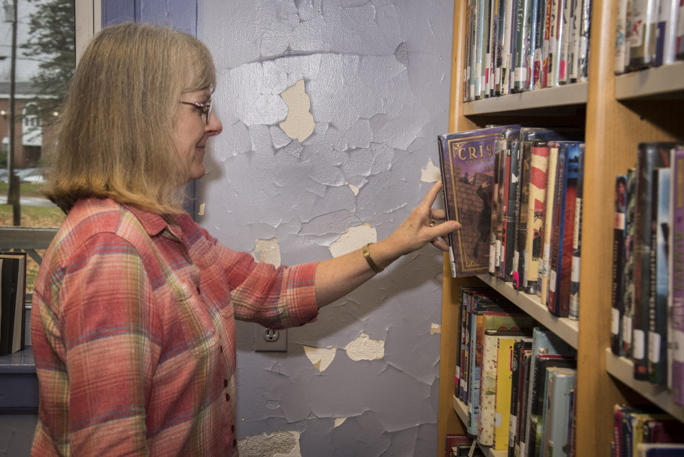 Lynn Howker, Monmouth Middle School librarian, returns a book to the shelf Wednesday next to a library wall with chipped and cracked paint. The library is housed in a century-old building.