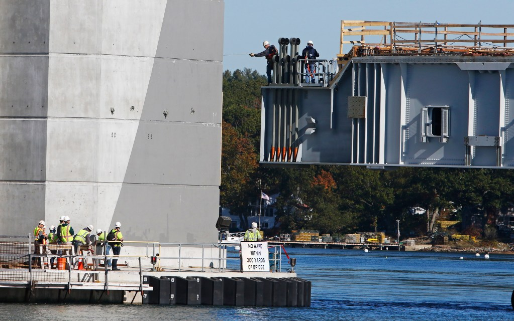 Dana Woods, center, a supervisor for Cianbro, measures for clearance from the span back to the bridge tower as the span is positioned for attaching to the Sarah Mildred Long Bridge between Kittery and Portsmouth, N.H.