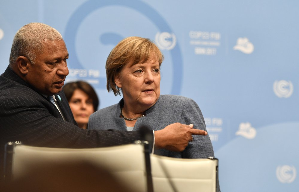 Fiji prime minister and COP president Frank Bainimarama, left, talks to German Chancellor Angela Merkel during the 23rd Conference of the Parties (COP) climate talks in Bonn, Germany, Wednesday.