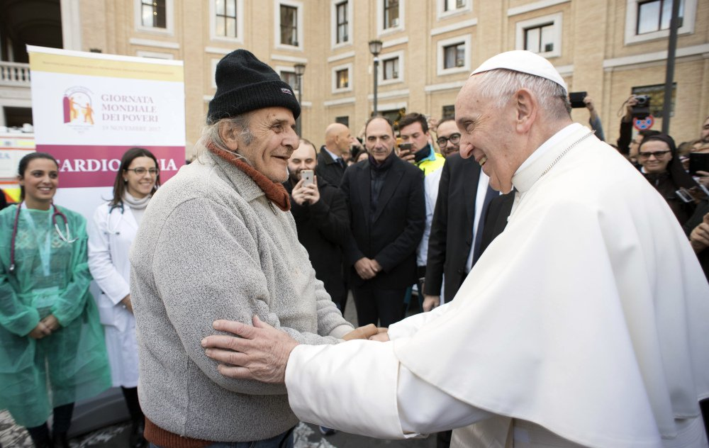 """L'Osservatore Romano via AP Pope Francis greets an unidentified man during a surprise visit to a small facility near St. Peter's Square where doctors on a volunteer basis give poor people medical exams, Thursday. Francis decried that, increasingly, only the privileged can afford sophisticated medical treatments and urged lawmakers to ensure that health care laws protect the """"common good."""""""