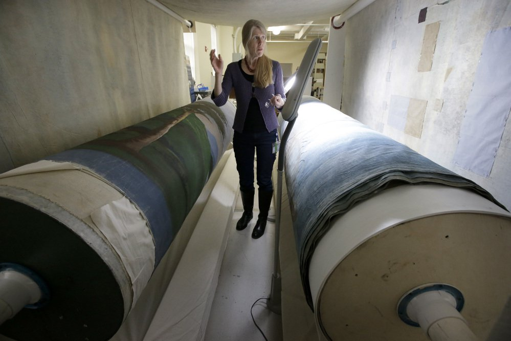 """Textile conservator Kate Tarleton of Rochester, Mass., stands between two oversized spools holding part of the """"Grand Panorama of a Whaling Voyage Round the World,"""" at the New Bedford Whaling Museum in Massachusetts."""