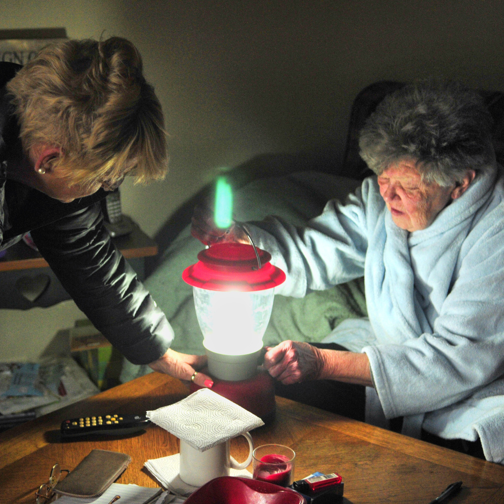 Karen Anderson, left, visits with her neighbor Leona Russell on Wednesday in Farmingdale's Hayford Heights neighborhood, which was still without power. Anderson, who has been bringing Russell meals, brought over the lantern to lend it to her.