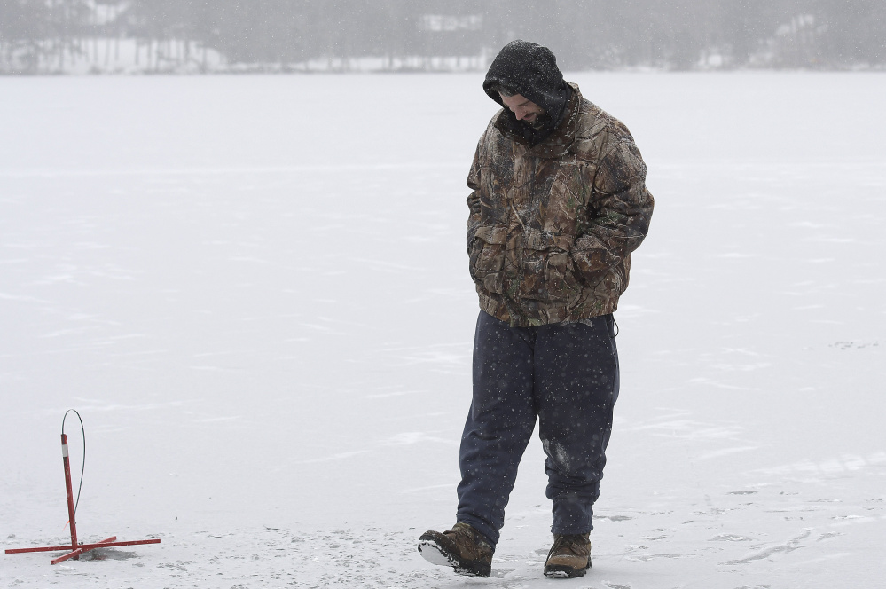 "Billy Gayton, of Leeds, waits Monday for a flag while ice fishing on Cochnewagon Lake in Monmouth. Gayton measured 5 inches of ice along the shore, where he placed traps, and 3 inches about 100 yards out. The shelf encouraged him to wait patiently in freezing temperature to catch a fish. ""I got to take care of that itch somehow,"" he said."