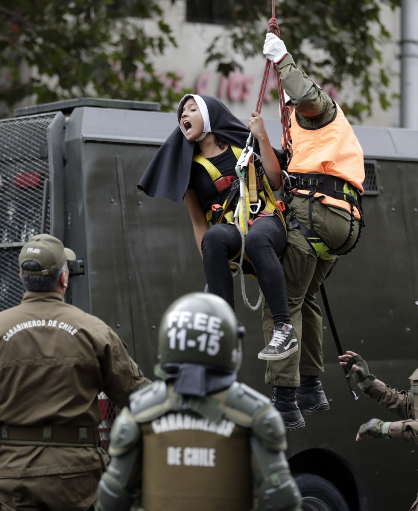 An activist dressed as a nun is lowered down by a police officer and detained, after protesters placed a pro-abortion banner above a road near Pope Francis' expected route.