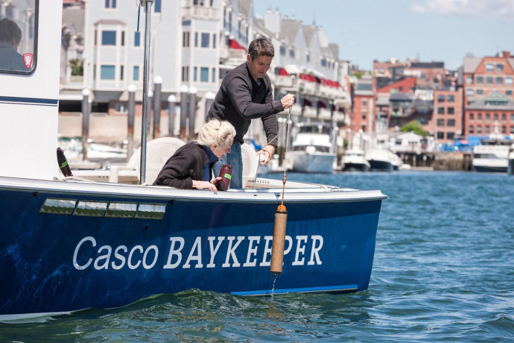 Friends of Casco Bay Executive Director Cathy Ramsdell and Mike Doan, research associate, collect water samples in Portland Harbor.