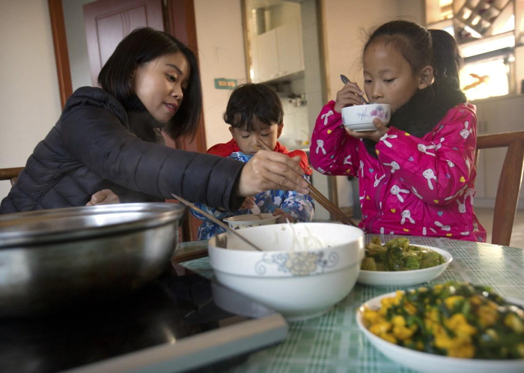 Deng Guilian, wife of Chinese labor activist Hua Haifeng, (below with their son Bo Bo, 4) eats lunch with their daughter, Chen Chen, 7, and Bo Bo in their home on the outskirts of Xiangyang in central China's Hubei Province.