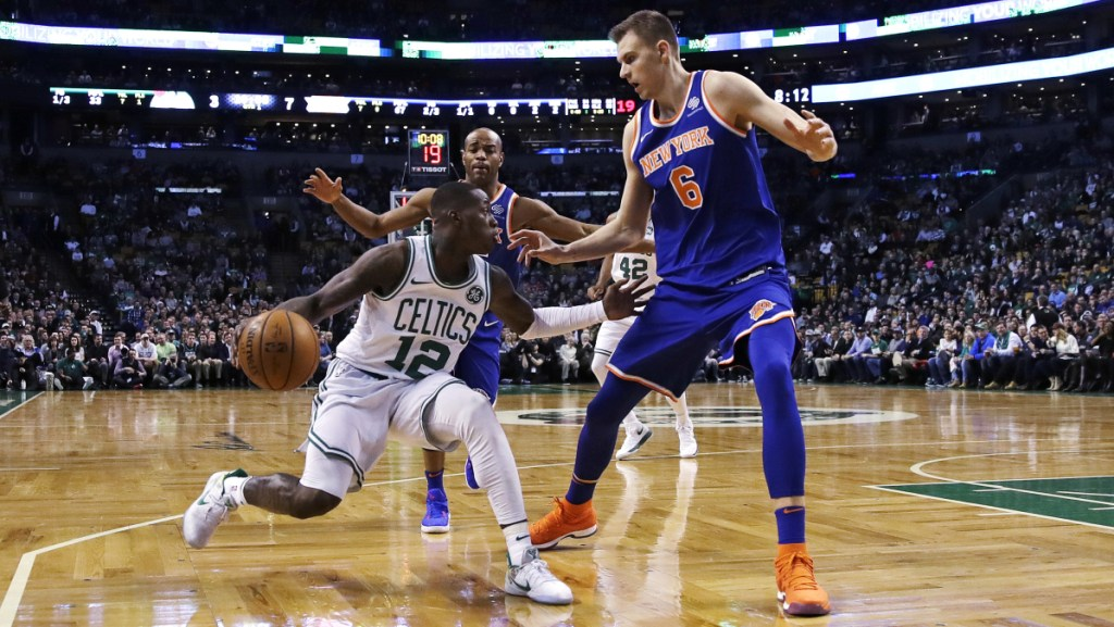 New York's Kristaps Porzingis tries to trap Boston's Terry Rozier on a drive to the basket during the first quarter Wednesday night in Boston.