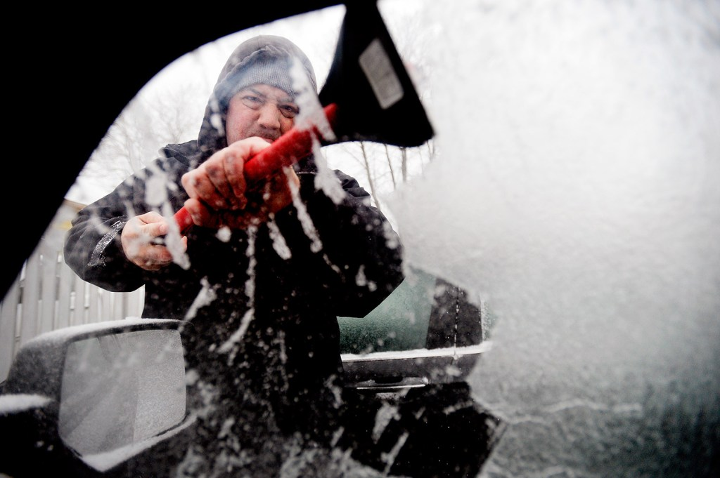 Joseph Albino, of South Portland, scrapes ice off his vehicle's windows before heading off to work Tuesday morning.