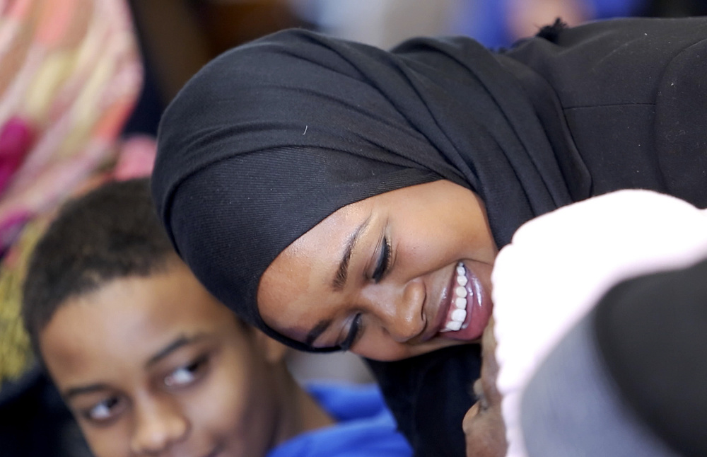Zahra Abu speaks with family members Friday before her swearing-in ceremony at Portland City Hall. Five new members joined the Portland Police Department, including Abu, Maine's first Somali officer.