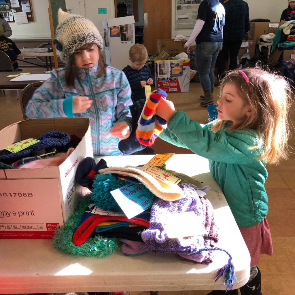 Eleanor Gagne, 7, left, and Emma Karnes, 5, both of Hallowell, help sort and tag donated winter hats at the Martin Luther King Jr. Day of Service on Monday at the Augusta Community Warming Center.