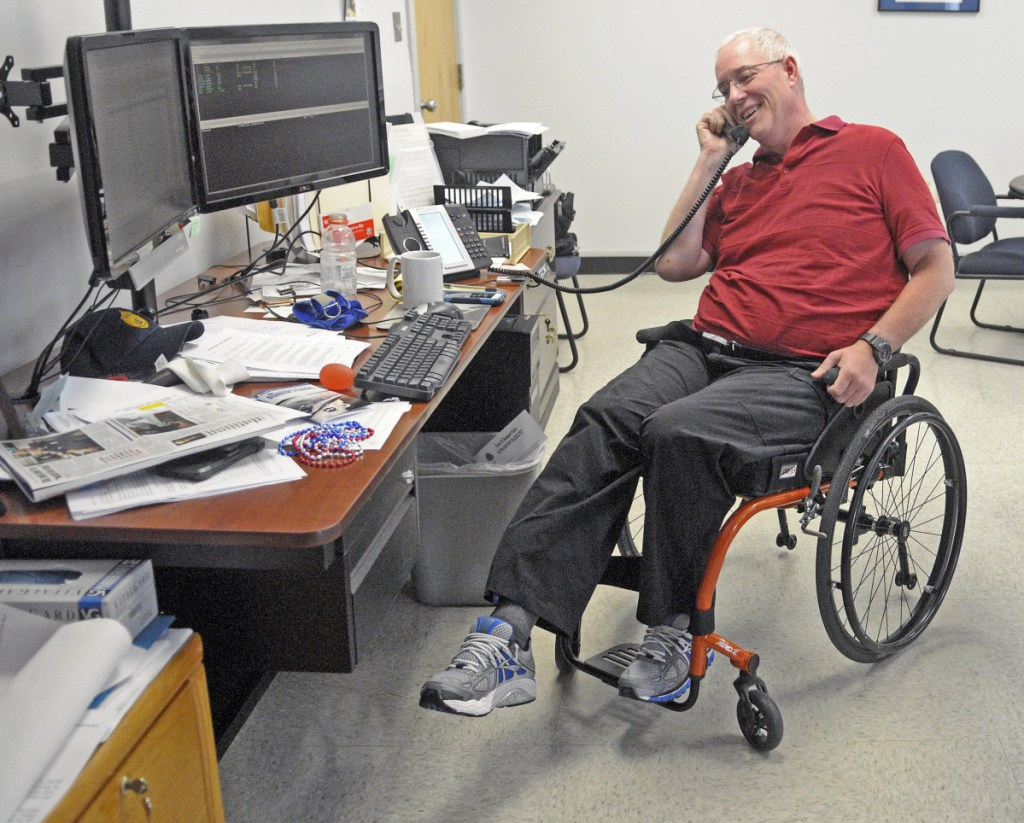 Chief Robert Gregoire, of the Augusta Police Department, does leg lift exercises while talking on the phone July 9, 2015, in his manual wheelchair at police headquarters in Augusta. Gregoire plans to retire as police chief in about four months.
