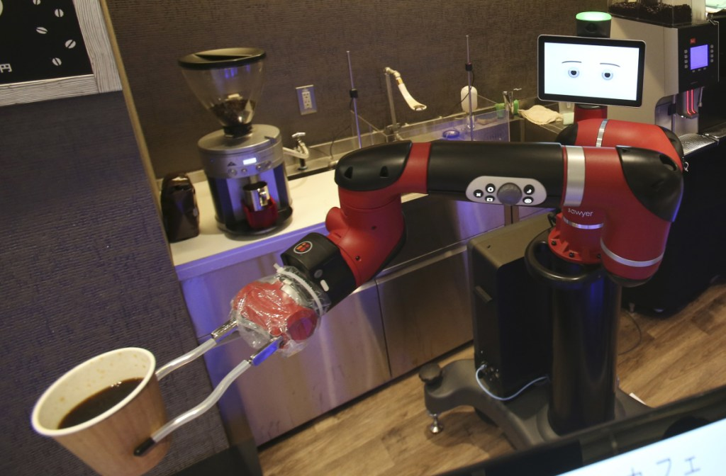 """Sawyer, a robot barista, makes a coffee at Henn-na Cafe in Tokyo on Friday. """"I can make one better than human beings around here,"""" the robot says."""