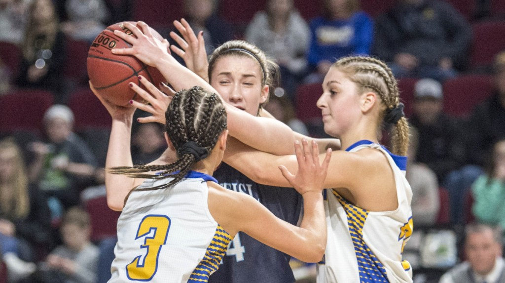 Presque Isle's Maggie Castonguay (24) looks to pass the ball as she draws a double-team by Hermon's Alex Allain (3) and Maddie Pullen during a Class B North semifinals game Wednesday at the Cross Insurance Center in Bangor.