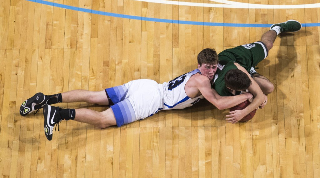 Hermon's Garrett Trask, left, and Mount Desert Island's James McConomy try to get control of a loose ball during the Class B North championship game Saturday at the Cross Insurance Center in Bangor.