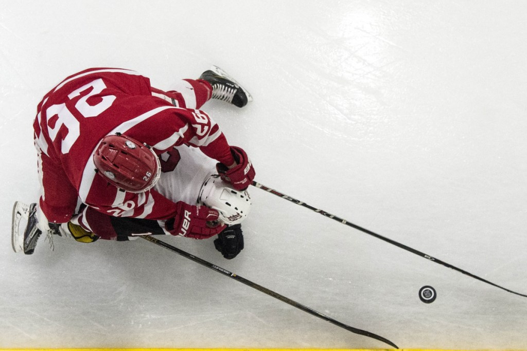Bangor's Josh Sherwood (12) tries to maintain control of the puck as he falls to the ice while Cony's Joseph Arps (26) tries for the steal Tuesday in Bangor.