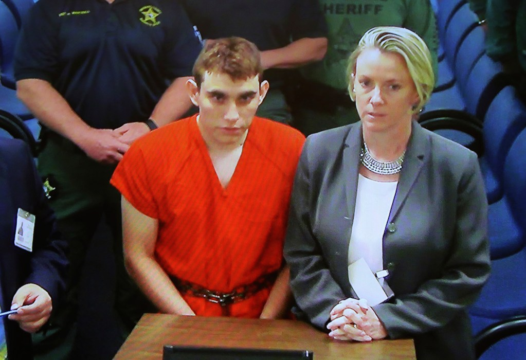 A video monitor shows school shooting suspect Nikolas Cruz, left, making an appearance in Broward County Court on Thursday in Fort Lauderdale, Florida. Cruz is accused of opening fire Wednesday at a high school in Parkland, killing least 17 people.