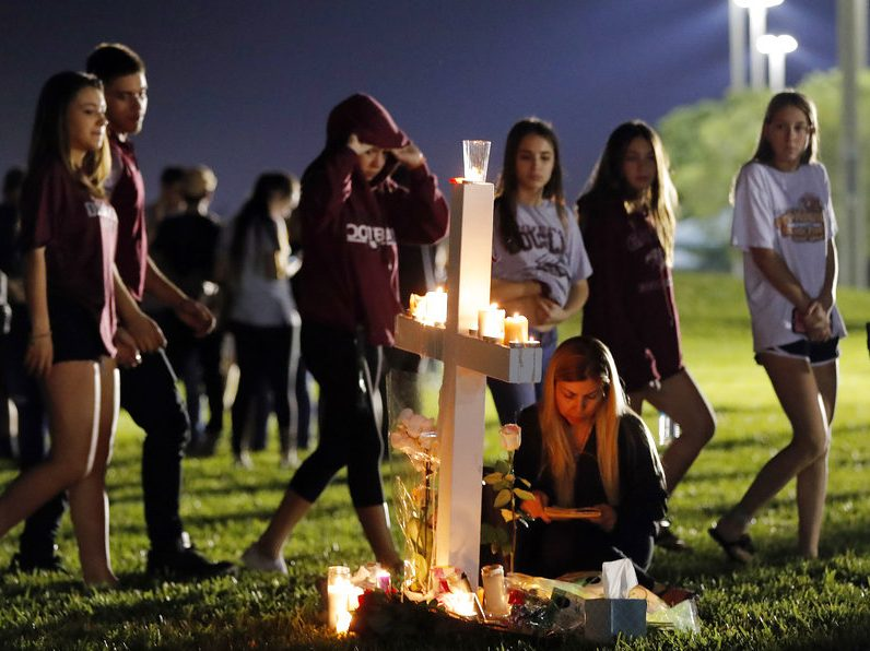 Students walk past one of seventeen crosses after a candlelight vigil for the victims of the Wednesday shooting at Marjory Stoneman Douglas High School, in Parkland, Fla., Thursday.