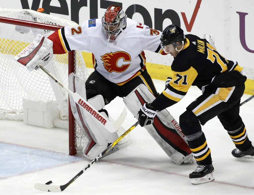 Evgeni Malkin gathers the puck and prepares to put it behind Calgary goaltender Jon Gillies, of South Portland, in the first period Monday night in Pittsburgh. The Penguins won in OT.