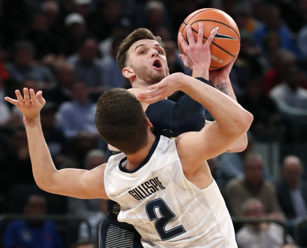 Marquette guard Andrew Rowsey (30) collides with Villanova guard Collin Gillespie (2) during the second half of an NCAA college basketball game in the Big East men's tournament quarterfinal in New York, Thursday, March 8, 2018. Villanova defeated Marquette 94-70. (AP Photo/Kathy Willens)