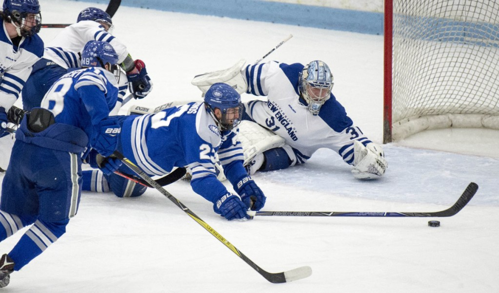 Colby College's Phil Klitirinos (23) is taken down in front of the University of New England net as Nor'easters goalie Tate Sproxton tries to recover during the first period Saturday of a NCAA Division III first-round tournament game at Harold Alfond Forum in Biddeford.