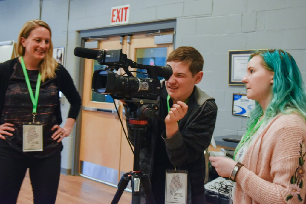 Kodi Quimby, center, 13 of Starks, looks through a video camera Saturday as documentary film instructor Erin Murphy, left, and student Sarah Thomas, 17, of Bangor, watch. The students are taking part in the Maine Student Film and & Video Conference in Waterville.
