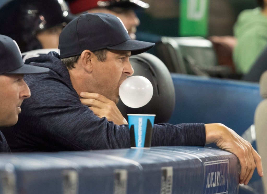 New York Yankees manager Aaron Boone blows a bubble with chewing gum in the sixth inning of a baseball game against the Toronto Blue Jays in Toronto, Friday, March 30, 2018. (Fred Thornhill/The Canadian Press via AP)