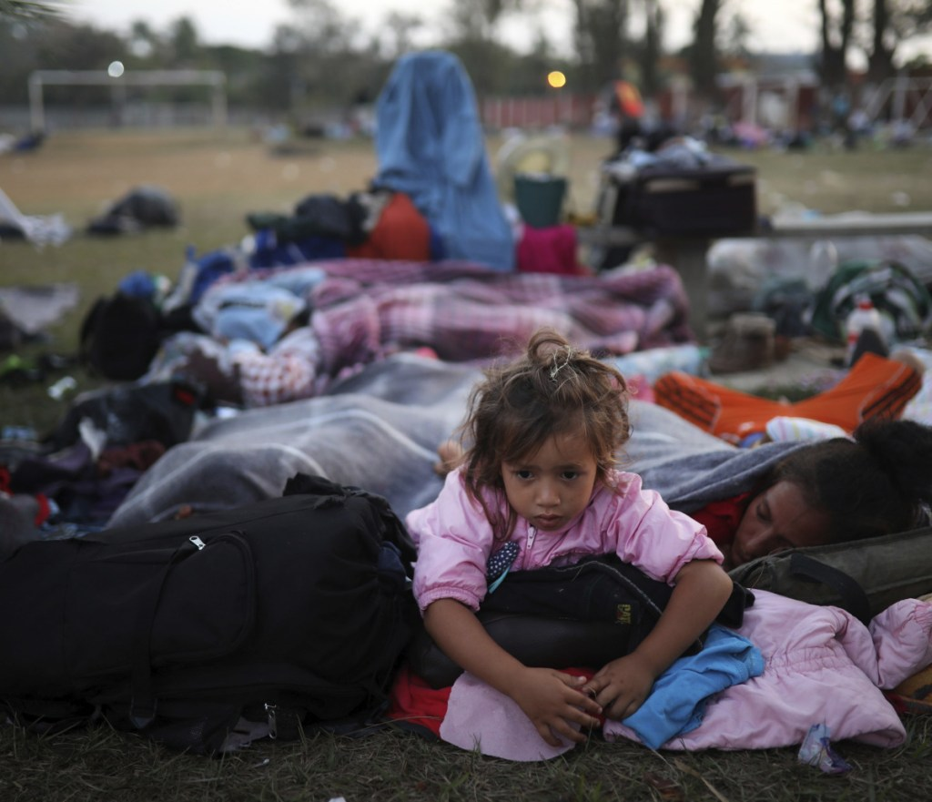 """A girl remains awake as Central American migrants traveling with the annual """"Stations of the Cross"""" caravan sleep at a sports club in Matias Romero, Mexico, on Tuesday."""