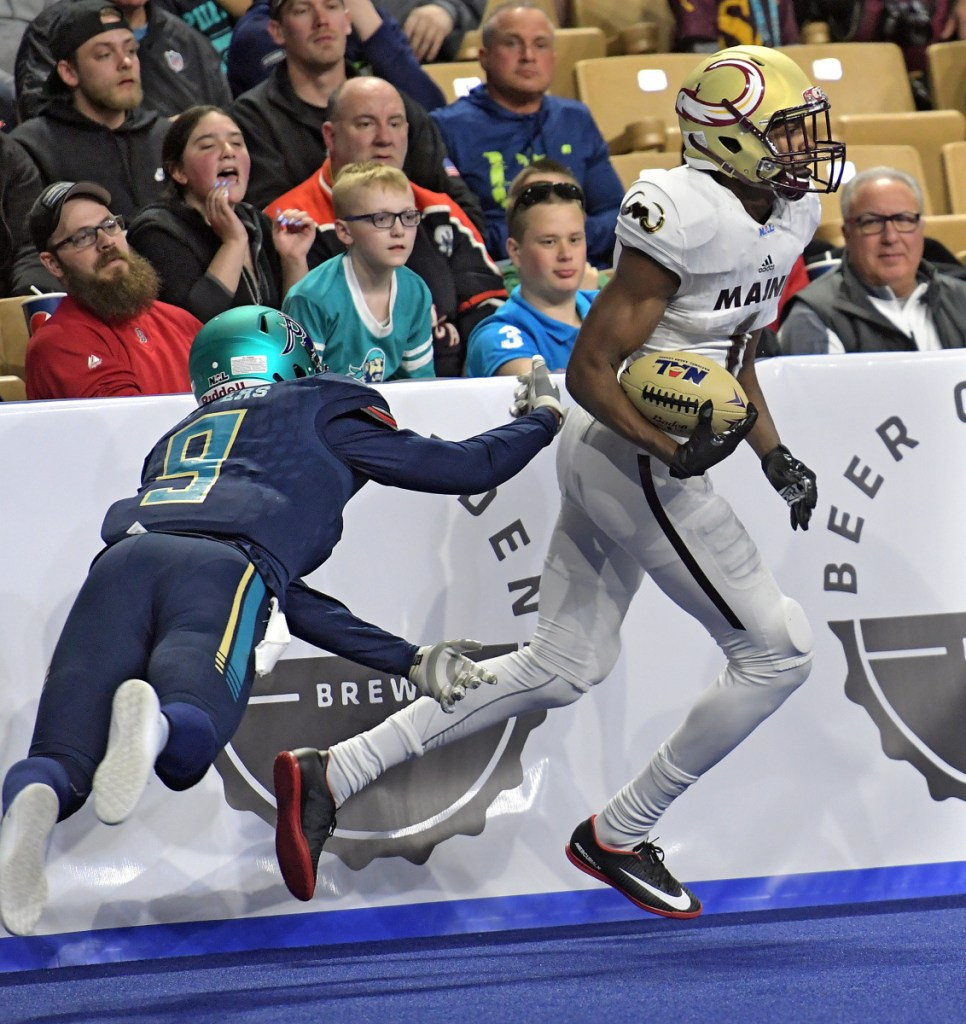 Derrick Macon of the Maine Mammoths eludes a tackle attempt by Troy Sanders of the Massachusetts Pirates during a boisterous franchise debut Saturday night.