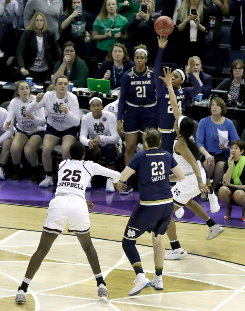 Notre Dame's Arike Ogunbowale, top, sinks a 3-point basket to defeat Mississippi State 61-58 to win the NCAA women's national championship in Columbus, Ohio.