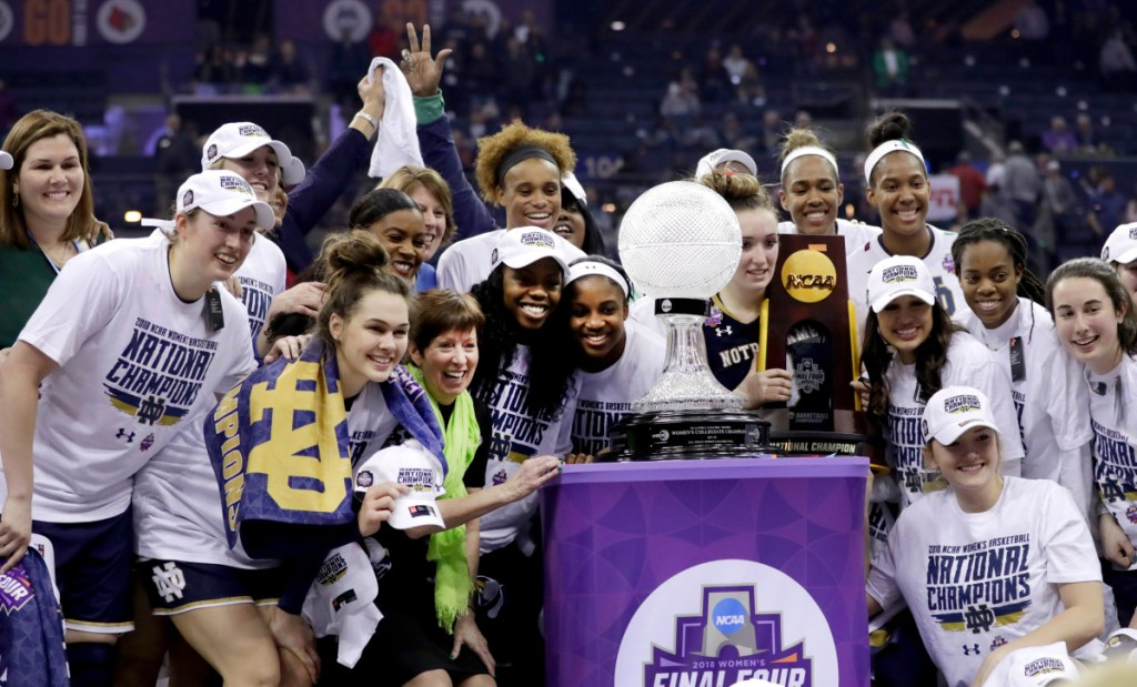 Members of the Notre Dame women's basketball team celebrate with the trophy after defeating Mississippi State for the national championship Sunday in Columbus, Ohio.