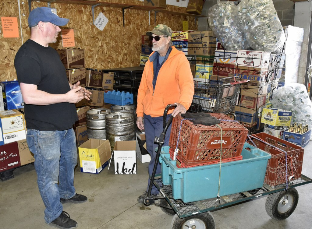 Harold LaBrie, right, speaks with Damon's Beverage employee Bobby Frappier after bringing returnable cans and bottles in a cart to the redemption room in Waterville on Wednesday. LaBrie's bike that he used to transport containers was stolen and Frappier offered him a bike for free.