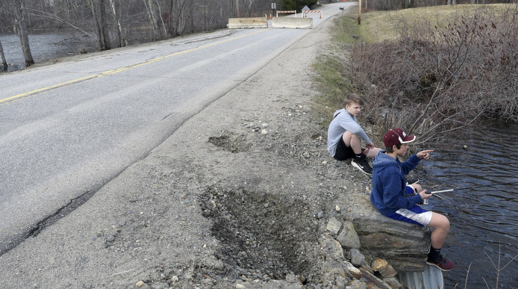Cam Armstrong, right, and Manny Calder fish Wednesday atop a culvert that washed out, forcing the closure of Sanborn Road in Monmouth. The road is closed until the town figures out how finance repairs. The Monmouth Academy students were searching for fish during spring break.