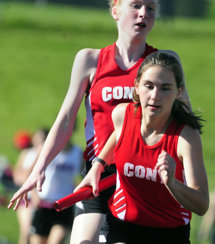 Cony's Cecelia Guadalupi, top, hands off the baton to teammate Ally Waller in the 4x800 relay during the I. Taylor Harmon Capitol City Classic last year at Cony.