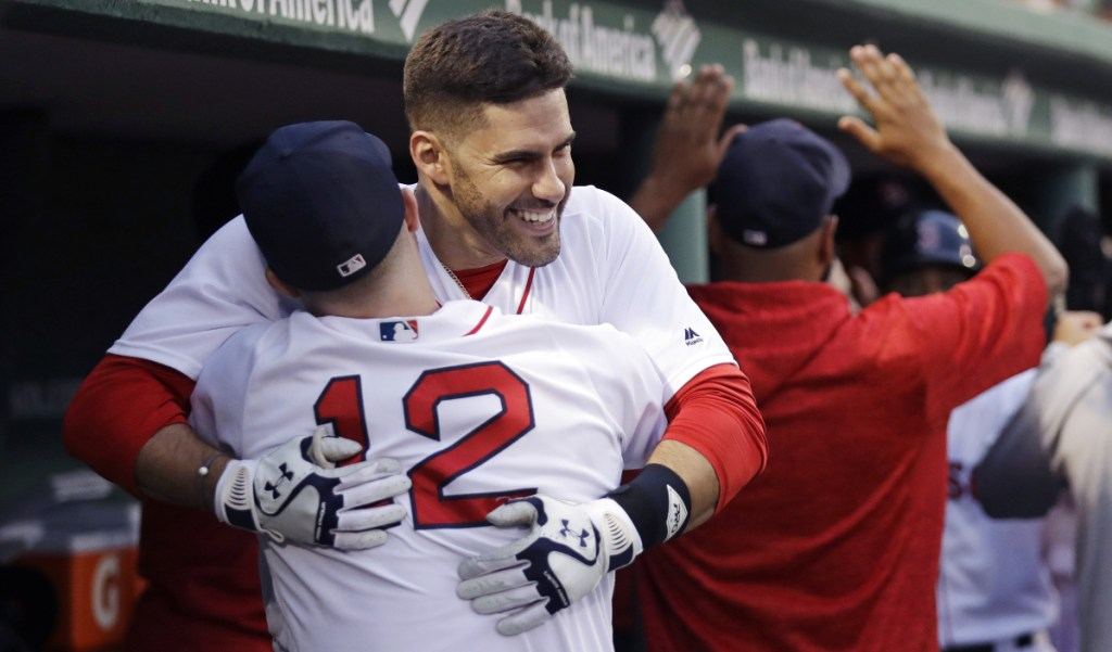 Boston Red Sox's J.D. Martinez is embraced by Brock Holt after belting a three-run home run off Los Angeles Angels starting pitcher Andrew Heaney in the second inning Wednesday night at Fenway Park.