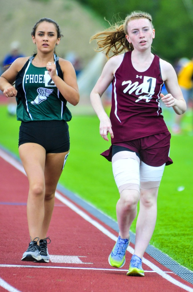 Staff photo by Joe Phelan   Spruce Mountain's Emily White, left, came in second with a 7:52.53 just behind Monmouth Academy's Moira Burgess's 7:52.43 in the 1,600 meter race walk at the Class C track and field state meet Saturday in Waterboro.