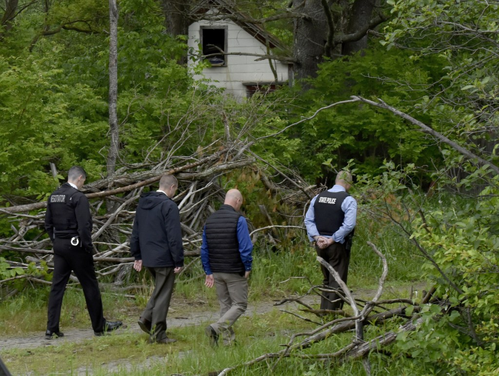 Maine State Police detectives walk toward the site on Tuesday where an excavator is digging for clues at an abandoned building, background, off Route 150 in Skowhegan, as police continue their investigation into the disappearance of Tina Stadig, who has been missing for more than a year.