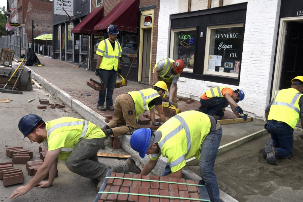 Masons lay bricks on the new sidewalk along Route 201 in downtown Hallowell on Monday as part of a large reconstruction project. Officials say this and other projects won't be affected by political wrangling over voter-approved bonds intended to pay for road construction.