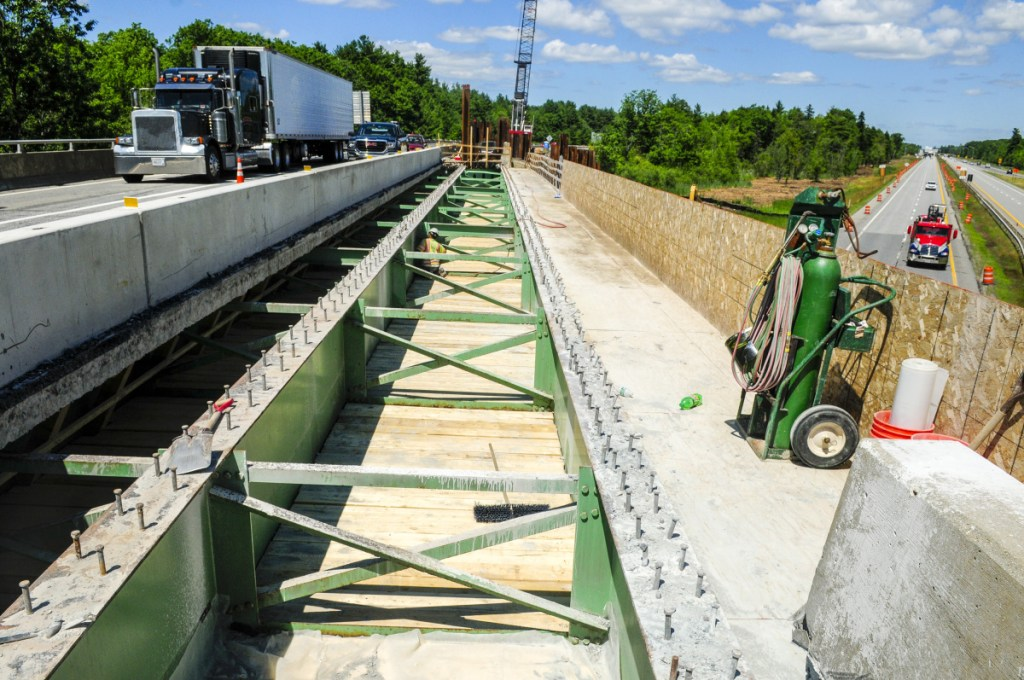 Wyman and Simpson employees work on re-decking an overpass that carries southbound traffic from Interstate 95's Exit 103 over the highway to the Interstate 295 toll booth on Wednesday in West Gardiner.