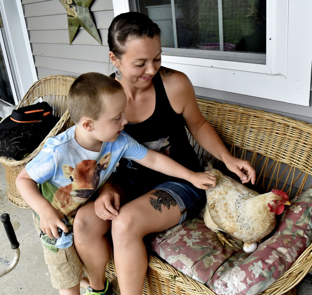 Athens farmer Kassie Dwyer and her son, Joey, try to coax a hen named Stumps off a porch couch Tuesday to see how many eggs she is sitting on at the Eden farm in Athens. Dwyer is launching an effort to enact an Athens Food Sovereignty Ordinance, which would allow consumers to buy directly from local farmers and food producers without state and federal licensing and inspections.