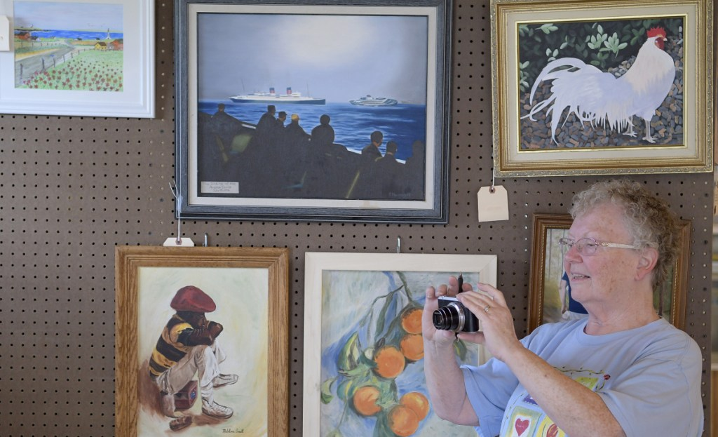 Marilyn Stinson photographs the display she arranged Tuesday for the Enterprise Grange, of Richmond, in the exhibition hall at the Pittston Fairgrounds. The Pittston Fair starts Thursday and wraps up Sunday.